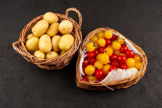 Vista dall'alto patate e pomodori all'interno dei cestini al buio