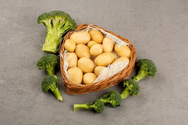 Vista dall'alto patate con broccoli verdi freschi maturi su sfondo grigio