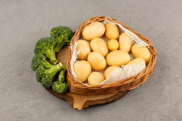 Vista dall'alto patate con broccoli verdi su sfondo grigio