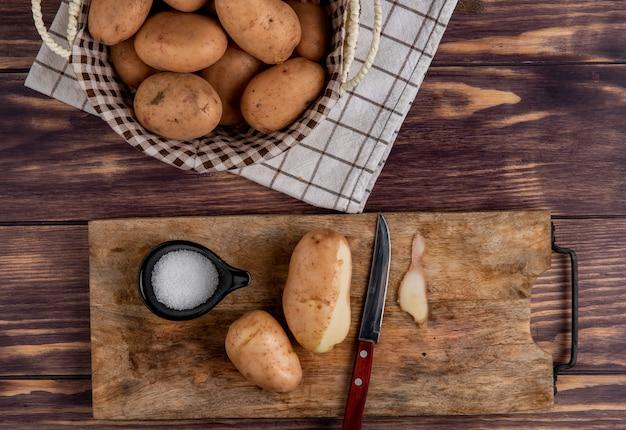 Vista superiore delle patate con il coltello e il sale delle coperture sul tagliere con altri quelli in cestino sul panno su legno