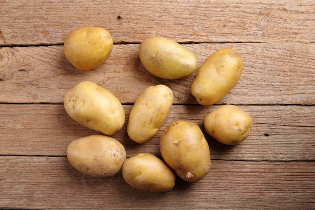 Top view potatoes on wooden background