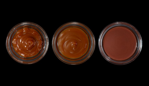 Top view of pots with caramel, cocoa butter and chocolate oil