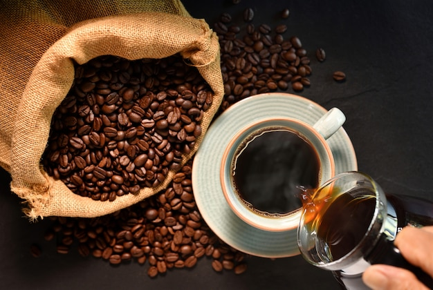 Top view of pouring coffee with smoke on a cup and coffee beans on burlap sack on black background