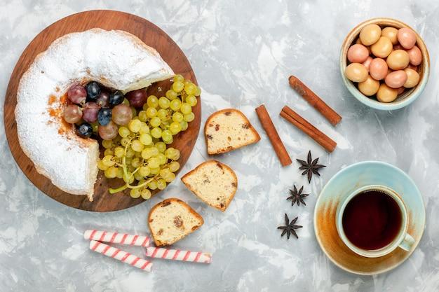 Vista dall'alto torta in polvere deliziosa torta al forno con uva fresca e tazza di tè sulla scrivania bianca