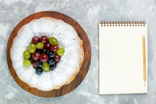 Vista dall'alto torta in polvere deliziosa torta al forno con uva fresca e blocco note sulla scrivania bianca