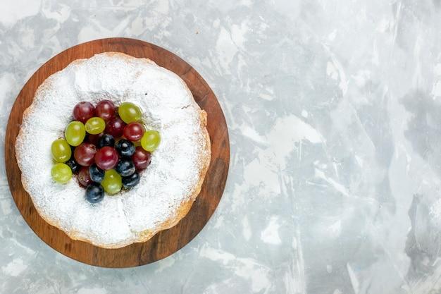 トップビュー粉ケーキ白い机の上に新鮮なブドウとおいしい焼きたてのケーキ