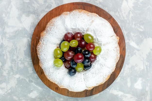 Vista dall'alto torta in polvere deliziosa torta al forno con uva fresca sulla scrivania bianca