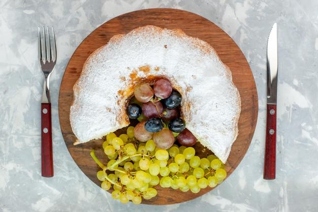 Torta in polvere vista dall'alto con uva fresca sulla scrivania bianca