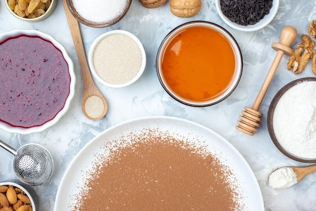 Vista dall'alto cacao in polvere su piatto rotondo ciotole di noci con marmellata farina di miele cucchiaio di legno bastone di miele sul tavolo
