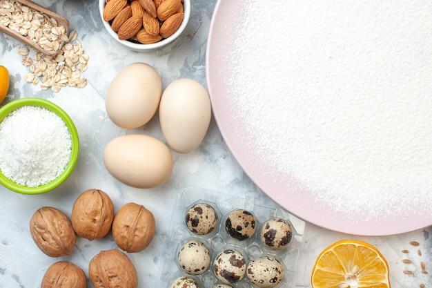 Вид сверху измельченной муки на тарелках с мукой и миндалем, грецкими орехами, перепелиными яйцами, овсяными хлопьями на столе