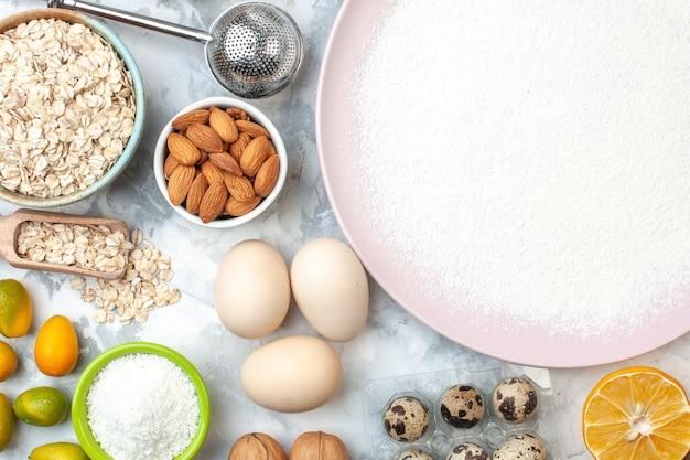 Vista dall'alto farina in polvere su ciotole con farina d'avena e mandorle noci uova di quaglia fetta di limone sul tavolo