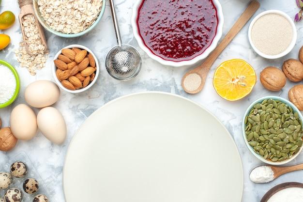 Vista dall'alto farina in polvere su piatti ciotole con avena semi di zucca semi mandorle marmellata arachidi uova uova di quaglia noci