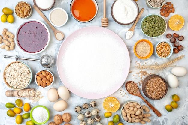 Vista dall'alto farina in polvere sul piatto cucchiaio di legno mandorle uova ciotole con marmellata miele semi di sesamo semi di zucca e altri animali
