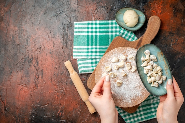 Vista dall'alto del processo di preparazione della zuppa di dushbere tradizionale azera e degli gnocchi su un asciugamano verde piegato a metà sul lato sinistro sulla superficie scura