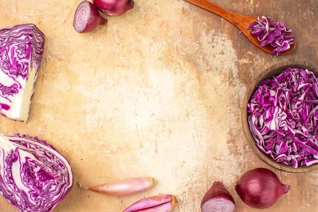 Vista dall'alto preparazione di cipolle rosse e cavoli per insalata di barbabietole fatta in casa su uno sfondo di legno con spazio di copia