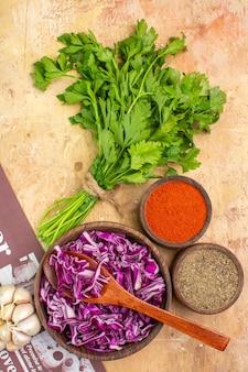 上面図木製のテーブルにサラダ用の黒胡椒ターメリック挽いた唐辛子のみじん切り赤キャベツのボウルと一緒にパセリにんにくの束を準備します