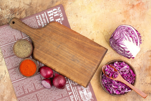 Top view prepare red onions a bowl of ground pepper and turmeric together with a bowl of red cabbage for beetroot salad on a wooden background
