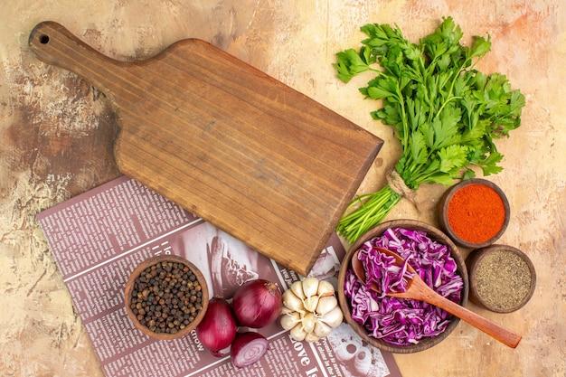 上面図木製のテーブルにサラダ用の黒胡椒ターメリック挽いた唐辛子赤キャベツのボウルと一緒にパセリの束と赤玉ねぎにんにくを準備します