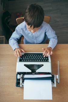 Взгляд сверху, preschool мальчик журналиста сидя на таблице и печатая машинка с карандашем на верхней части года. бизнесмен используя машинку на столе в офисе. бизнес и новые технологии.
