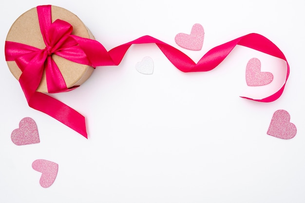 Top view of present with ribbon and hearts