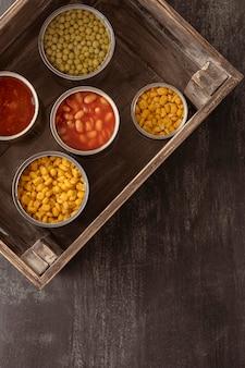 Консервированные продукты, вид сверху, в деревянном ящике с копией пространства