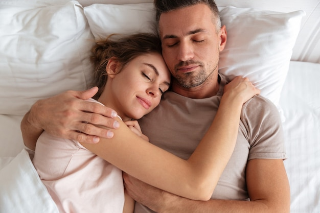Top view of pretty loving couple sleeping together in bed at home