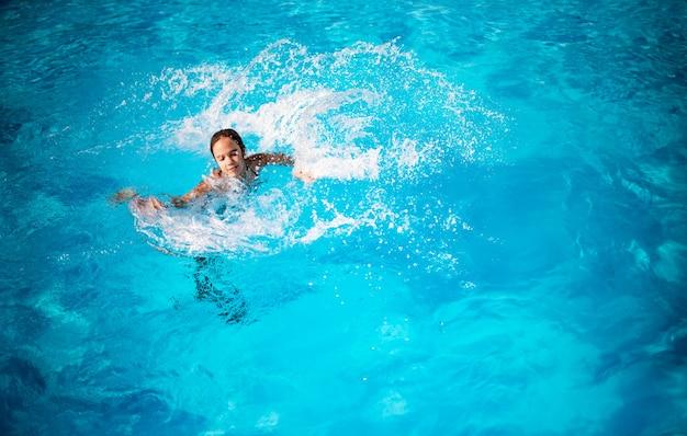 明るい日光の下でプールの青い澄んだ水に喜んではねかける上面図かわいい少女。ホテルと海でのリラクゼーションのコンセプト。
