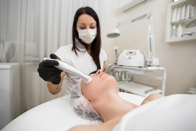 Top view of the procedure of non-injection mesotherapy for a young girl in the spa salon.