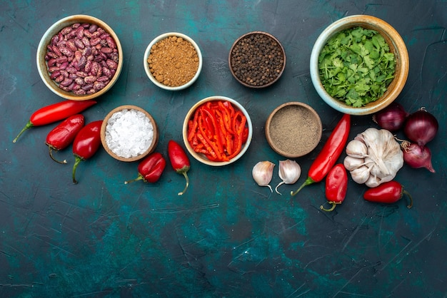 Top view product composition peppers onions garlics and greens with seasonings on the dark-blue background food ingredients product food meal vegetbale