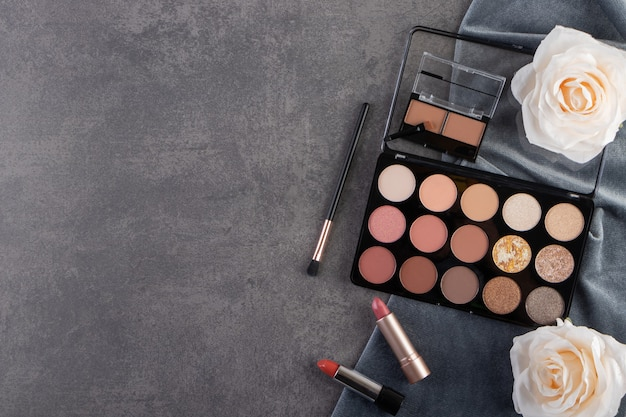 Top view of professional cosmetic product on grey surface with flowers