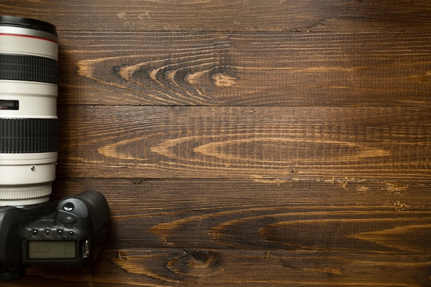 Top view of professional digital camera with telephoto lens on wooden background with copyspace