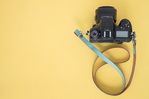 Top view of professional dslr camera on yellow background