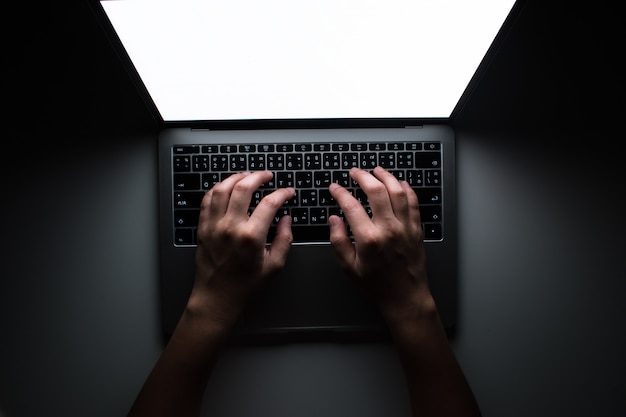 The top view of the programmer is working in a dark room on a white table.