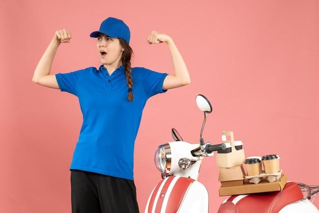 Vista dall'alto dell'orgogliosa donna del corriere in piedi accanto alla moto con caffè e piccole torte su di essa che mostra la sua muscolosa su sfondo color pesca pastello