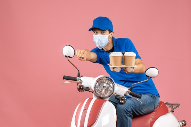 Top view of proud courier man in mask wearing hat sitting on scooter showing orders on pastel peach background