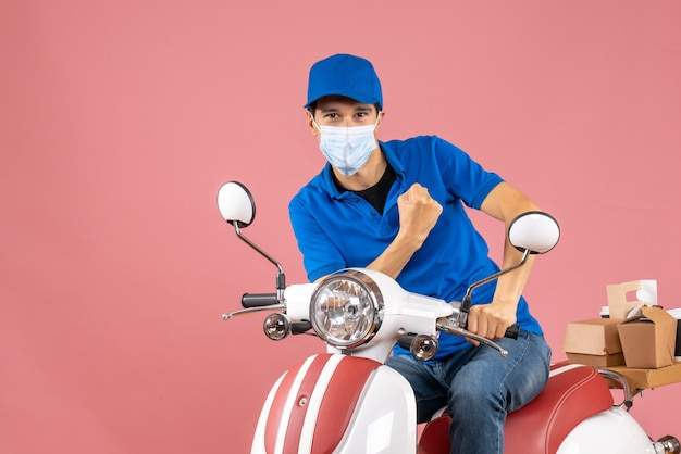Top view of proud delivery guy in medical mask wearing hat sitting on scooter on pastel peach background Free Photo