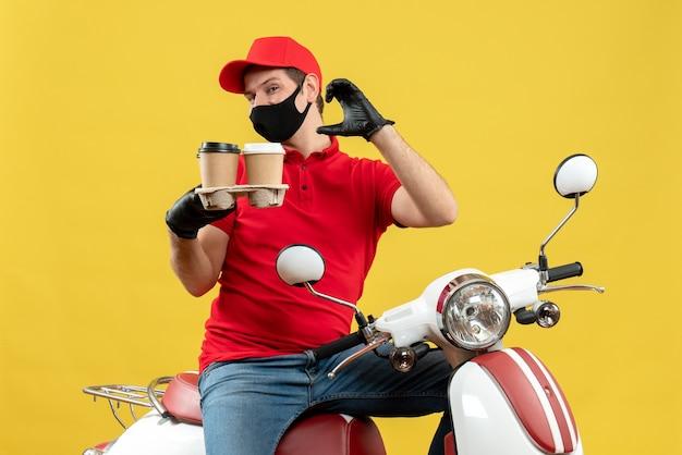 Vista superiore del fattorino orgoglioso che indossa guanti uniformi e cappello in maschera medica seduto su uno scooter che mostra ordini che fanno qualcosa di preciso