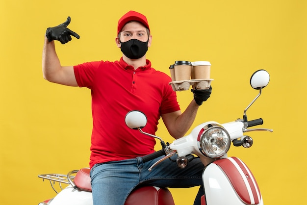 Top view of proud delivery guy wearing uniform and hat gloves in medical mask sitting on scooter showing orders