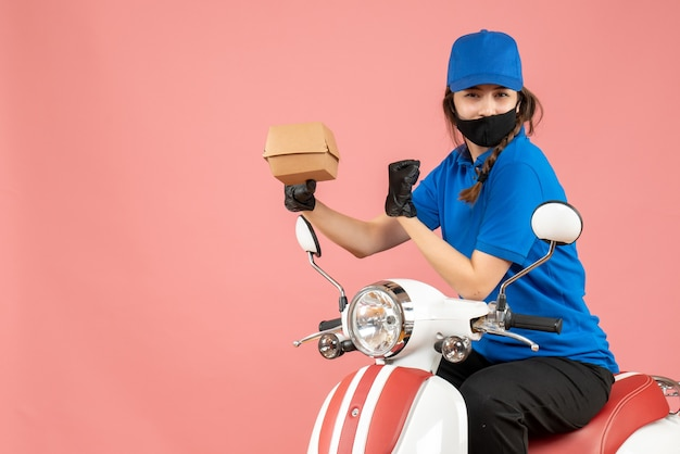 Top view of proud delivery person wearing medical mask and gloves sitting on scooter delivering orders on pastel peach background