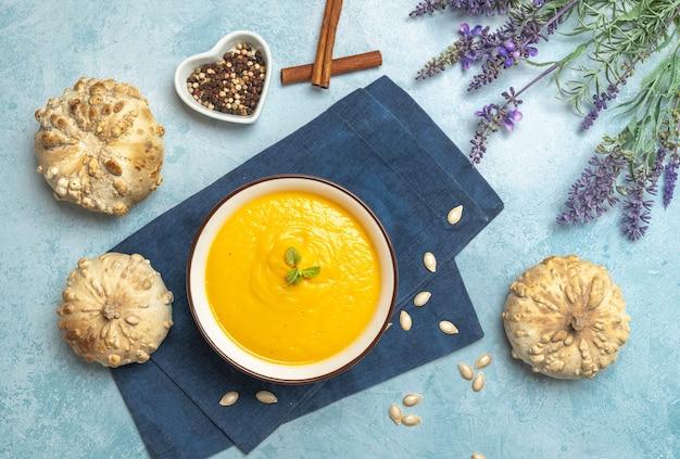 Vista dall'alto di una zuppa di crema di zucca circondata da zucche