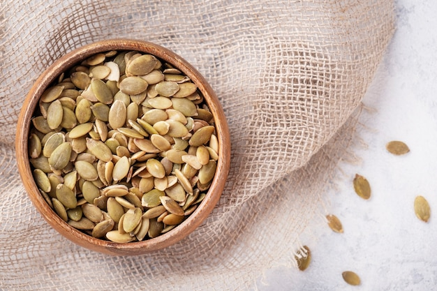 Top view of pumpkin seeds in a bowl. copy space