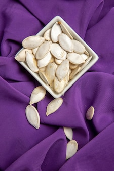 Вид сверху тыквенные семечки внутри тарелки на фиолетовой ткани цвета спелых фруктов в сыром виде