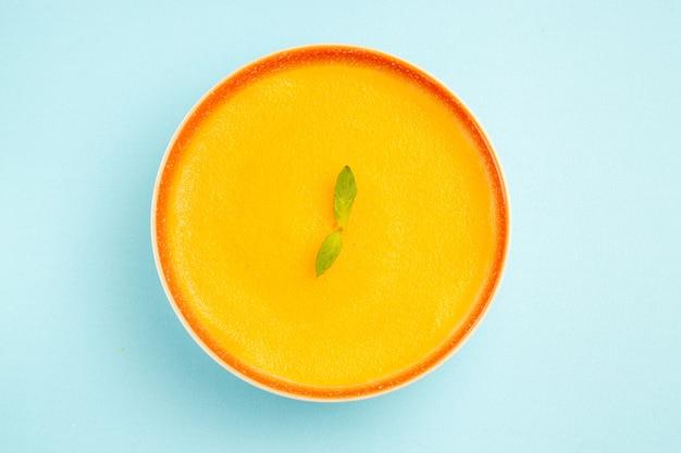 Vista dall'alto della zuppa di zucca all'interno del piatto su sfondo blu