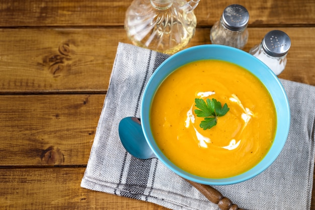 Top view of pumpkin soup with cream in blue plate and parsley