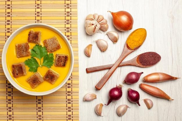 Vista dall'alto della zuppa di zucca con fette biscottate e aglio su bianco