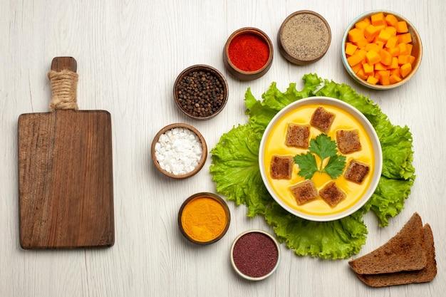 Vista dall'alto della zuppa di zucca con fette biscottate e condimenti su bianco