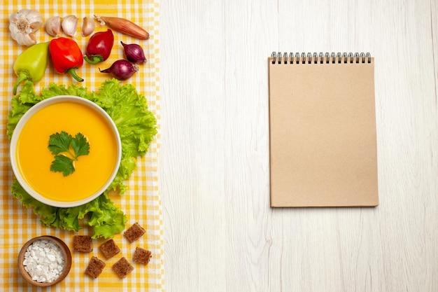 Vista dall'alto della zuppa di zucca con verdure su zuppa di piatto di frutta con pane bianco