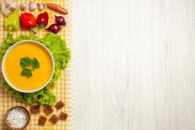 Vista dall'alto della zuppa di zucca con verdure su bianco