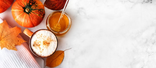 Top view of pumpkin spice latte or coffee with creamy foam, small orange pumpkin, white sweater and autumn leaves at white marble background. long banner. copy space