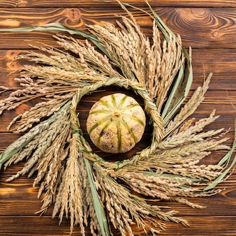 Top view pumpkin and wheat on wooden background